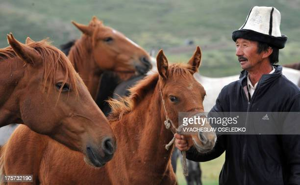 Man leads a horse at a pasture of the Suu-Samyr plateau 500 meters above the sea level, along the ancient Great Silk Road from Bishkek to Osh, some...