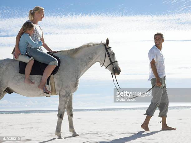 Man Leads a Horse With His Wife and Daughter Along the Beach