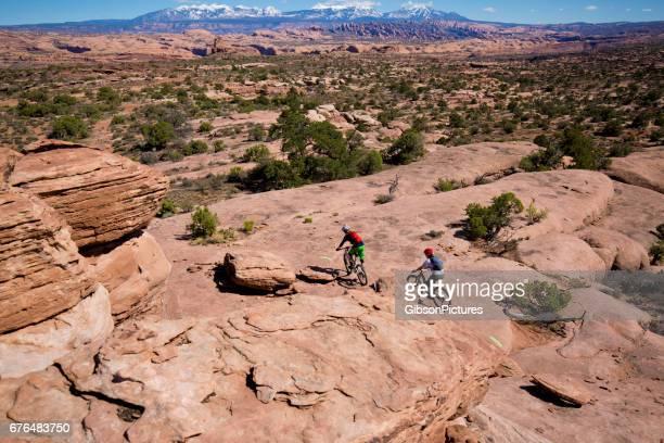 Ein Mann führt eine Frau auf einem cross-country Mountain Bike Ausritt in Moab, Utah, USA.