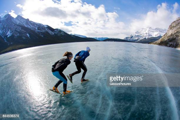a man leads a woman on a winter speed skating adventure on lake minnewanka in banff national park, alberta, canada. - winter sport stock pictures, royalty-free photos & images