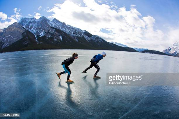 A man leads a woman on a winter speed skating adventure on Lake Minnewanka in Banff National Park, Alberta, Canada.