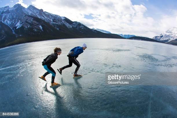 een man leidt een vrouw op een snelheid van de winter schaatsen avontuur op lake minnewanka in nationaal park banff, alberta, canada. - schaats ijs stockfoto's en -beelden