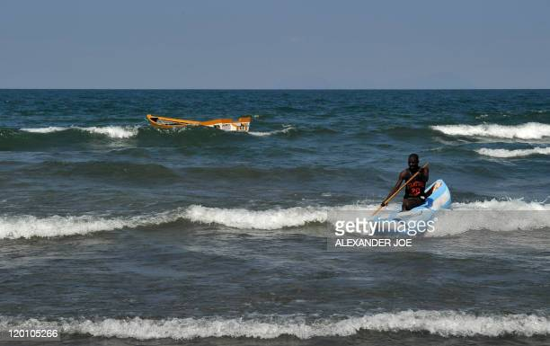 A man leads his traditional boat to shore at the Saga on Lake Malawi on July 17 2011 Lake Malawi remains unspoilt and one of Malawi's' biggest...