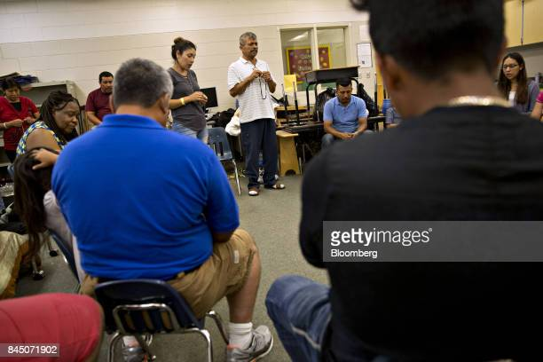 A man leads other spanish speaking shelter residents as they pray the Rosary in a classroom at Pizzo Elementary School an emergency shelter with over...