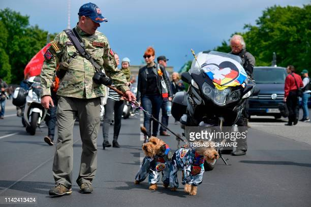 A man leads two dogs in camouflage suits with the flag of Russia during an event to commemorate the 74th anniversary of the victory over Nazi Germany...