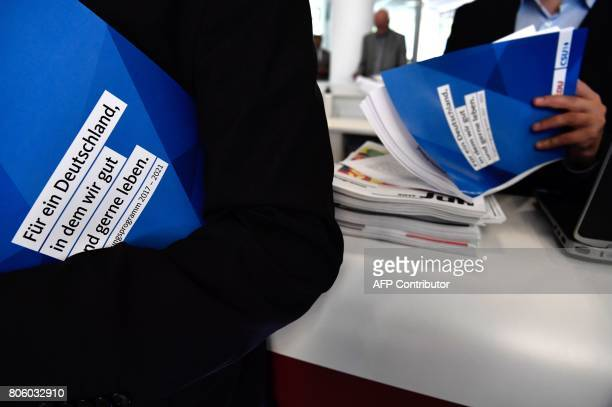A man leafs through the electoral programme of Germany's conservative CDU/CSU party union on July 3 2017 in Berlin / AFP PHOTO / John MACDOUGALL