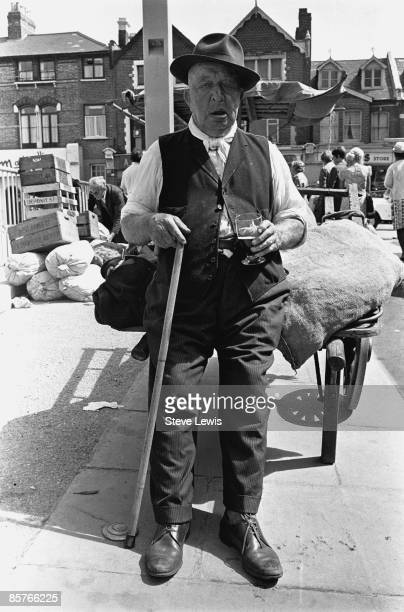Man leaning against a handcart in the East End of London, 1960s.