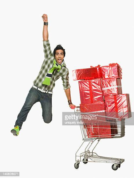 Man leaning against a shopping cart filled with gifts and cheering