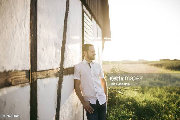 A man leaning against a timbered house at sunset.