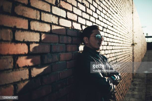 a man leaning against a wall - yusuke nishizawa stock pictures, royalty-free photos & images