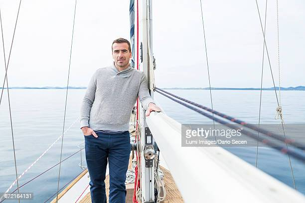 man leaning against boom of yacht - sail boom stock pictures, royalty-free photos & images