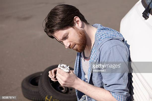 Man leaning against car looking at dipstick