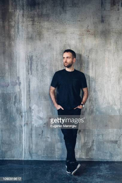 man leaning against concrete wall - t shirt stock pictures, royalty-free photos & images