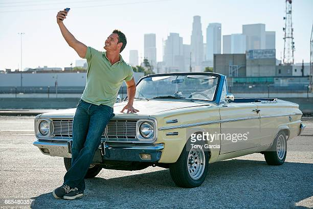 man leaning against convertible car taking selfie, los angeles, california, usa - showing off stock pictures, royalty-free photos & images