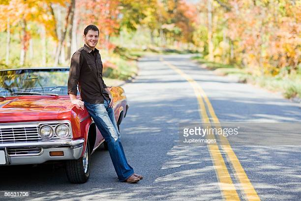 Man leaning against convertible on road