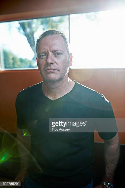 man leaning against counter, looking at camera. - tempe arizona stock pictures, royalty-free photos & images