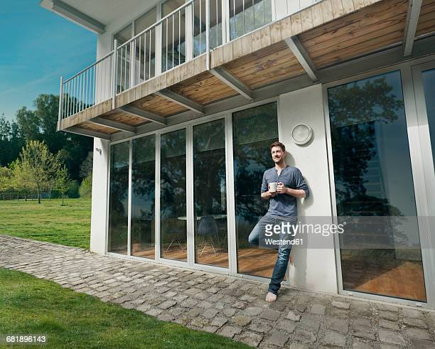 Man leaning against house front with a cup of coffee