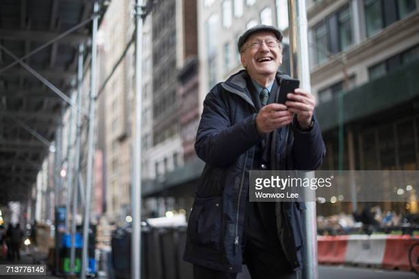 Man leaning against lamppost holding smartphone laughing, Manhattan, New York, USA