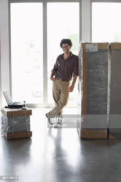 Man Leaning Against Large Package