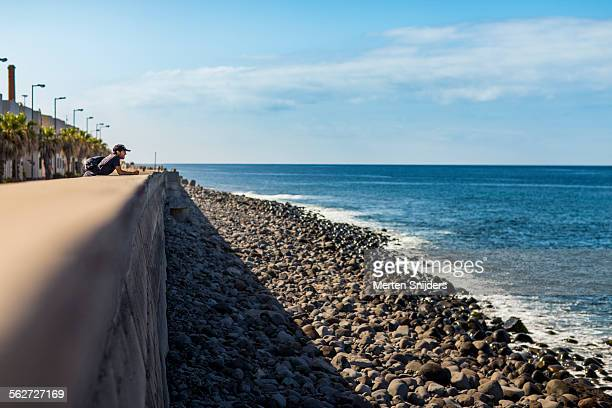 man leaning against oceanroad barrier - merten snijders stock-fotos und bilder