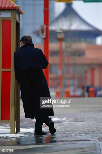 Man leaning against phone booth