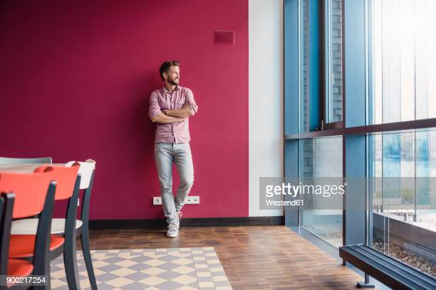 man leaning against purple wall in modern office looking out of window - lehnend stock-fotos und bilder