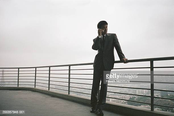 Man leaning against railing using mobile phone