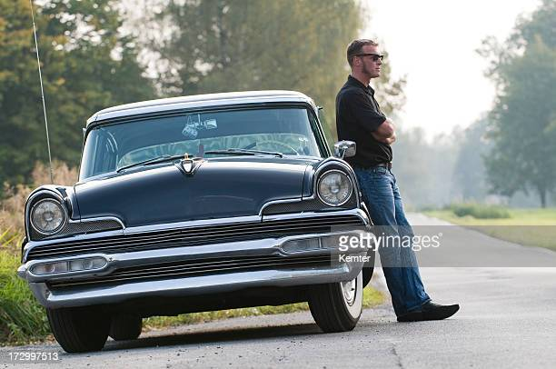 Man leaning against retro car on a back road