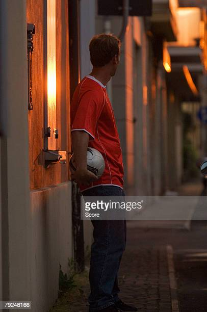 Man leaning against street wall with ball