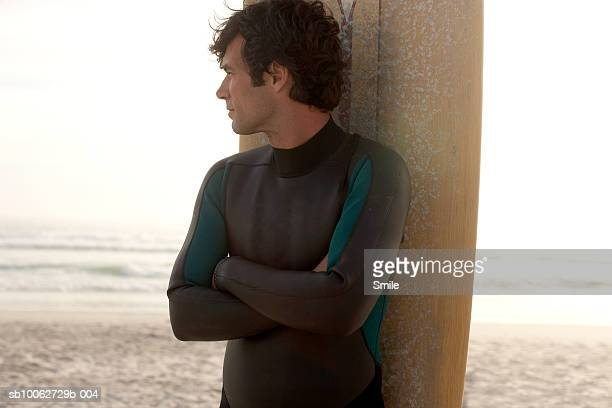 Man leaning against surfboard with arms crossed, standing on beach