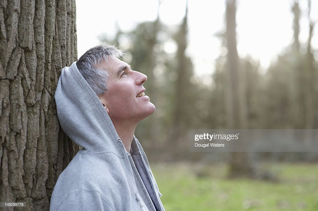 Man leaning against tree in countryside. : Stock Photo