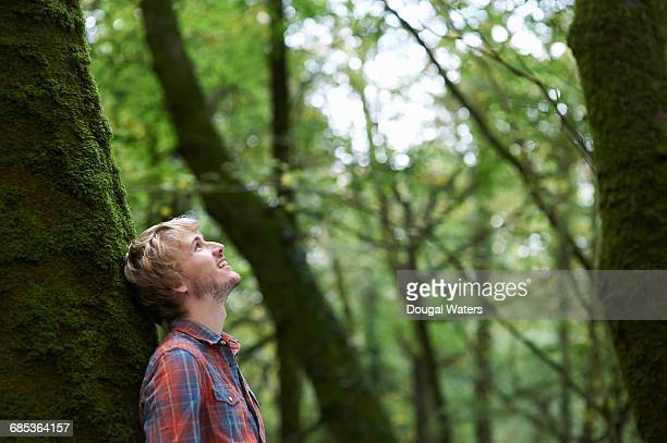 Man leaning against tree trunk in forest.