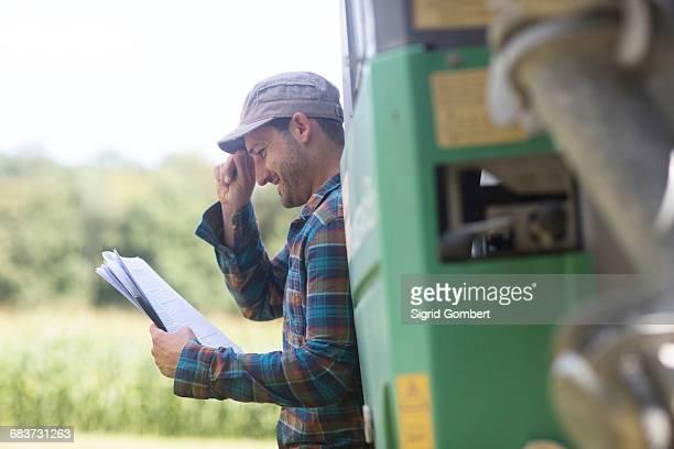 man leaning against truck looking at paperwork smiling - sigrid gombert stock-fotos und bilder