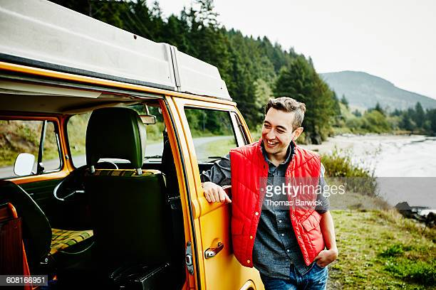 Man leaning against van parked on side of road