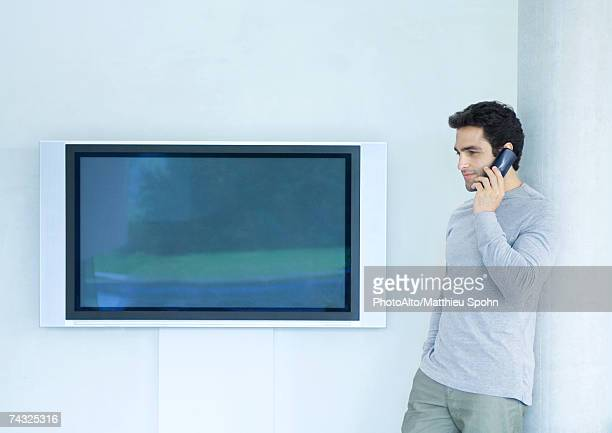 man leaning against wall using phone, next to widescreen tv - tela grande - fotografias e filmes do acervo