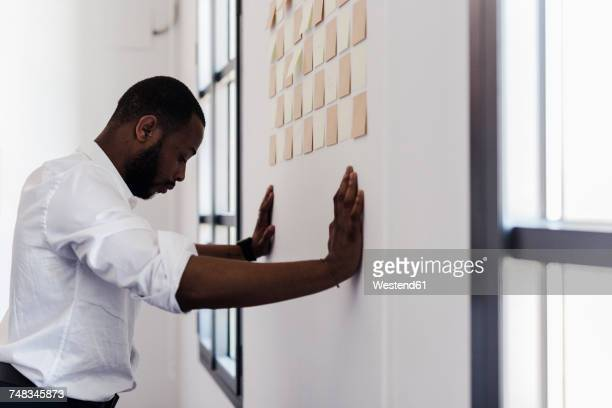 Man leaning against wall with adhesive notes in office