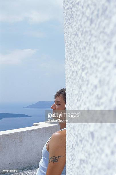 Man Leaning Against White Wall Outdoors