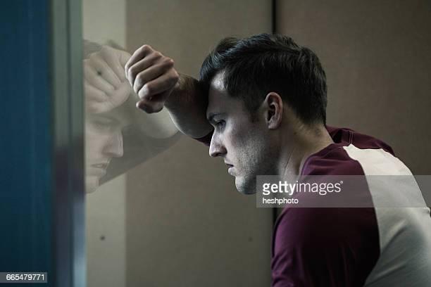 man leaning against window looking out - heshphoto stock-fotos und bilder