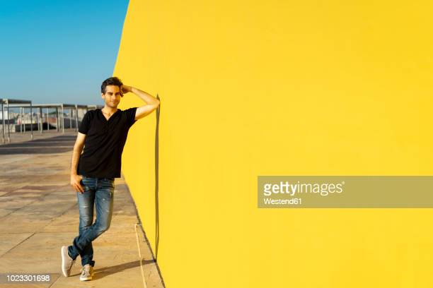 man leaning against yellow wall, smiling, thinking - lehnend stock-fotos und bilder