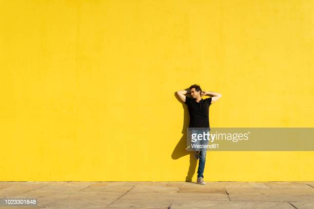 man leaning against yellow wall with hands behind head - hands behind head stock pictures, royalty-free photos & images