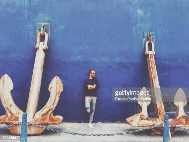Man Leaning Amidst Rusty Anchors Against Blue Wall