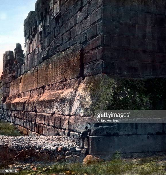 A man leaning at the Cyclop's wall of ancient Baalbek in the Lebanon 1920s