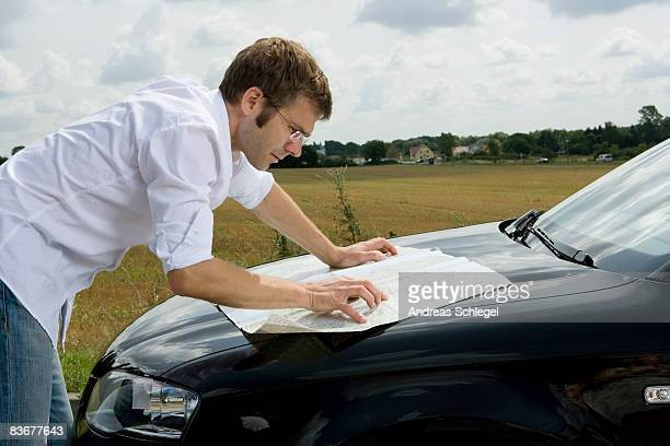 A man leaning on a car bonnet and reading a map