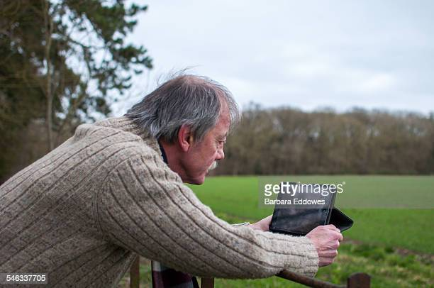 A man leaning on a metal fence using a tablet computer