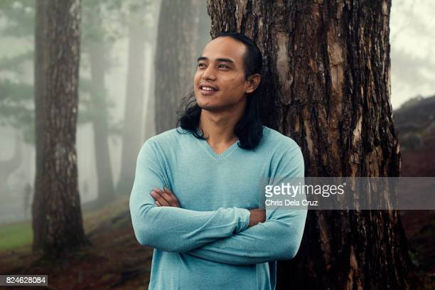 Man leaning on a pine tree smiling