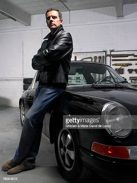 Man leaning on a Porsche in a garage.