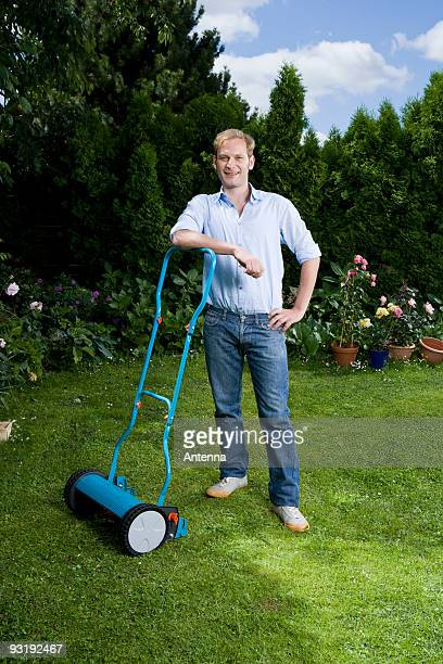 A man leaning on a push mower