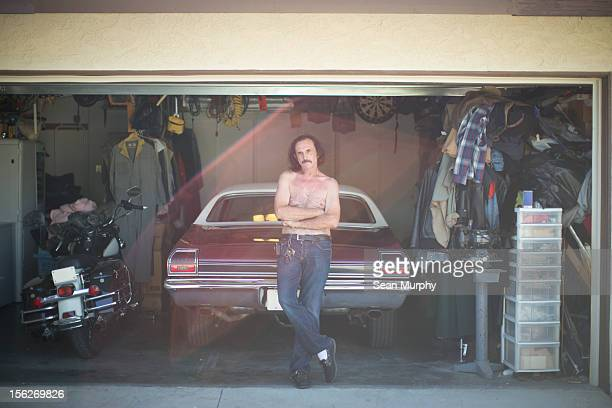 Man leaning on a vintage car in his garage