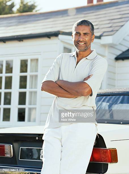Man leaning on back of car parked outside house, portrait