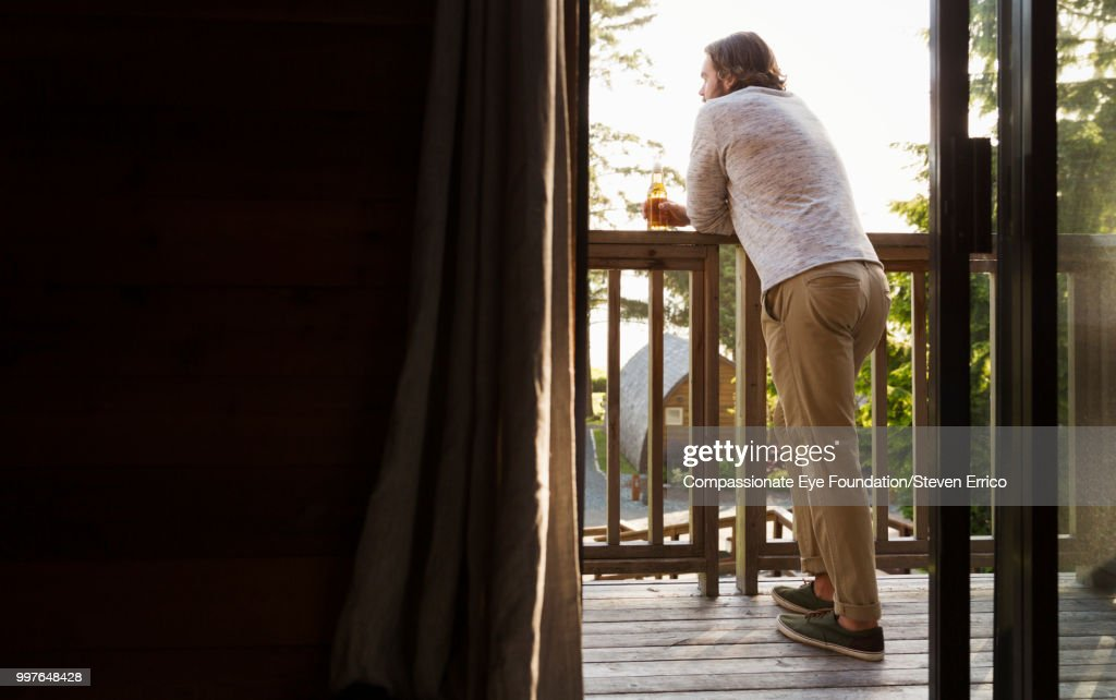 Man leaning on balcony looking at view : Stock Photo